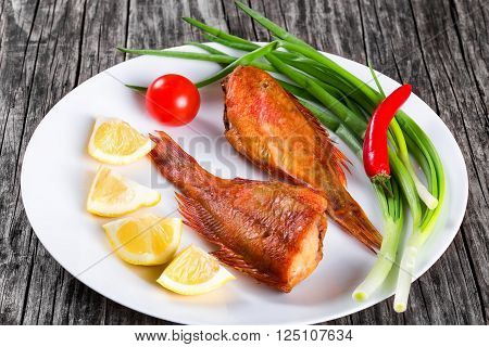 Red Sea Bass on awhite dish on an old wooden table with green spring onions lemon slices and cherry tomato on the background horizontal close-up