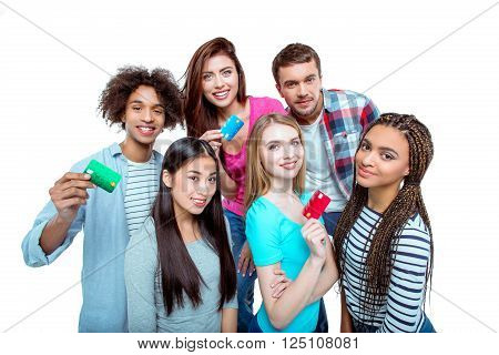 Studio shot of nice young multicultural friends. Beautiful people holding credit cards, looking at camera and smiling. Isolated background