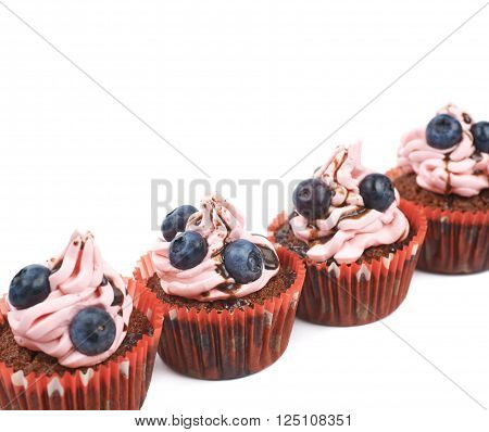 Chocolate muffin coated with the pink cream frosting and fresh bilberries, composition isolated over the white background, close-up crop fragment