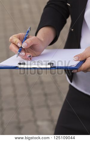 woman office worker holding a clip board with white paper