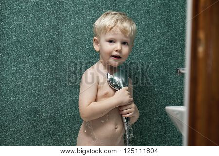 Baby boy bathes in a shower