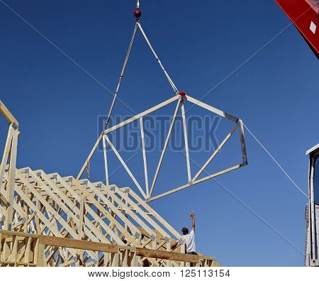 Man Reaching For Roof Truss With Carpenter Building Crew