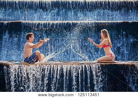 Happy family on honeymoon holidays - just married loving couple swimming and splashing with fun in waterfall pool. Active lifestyle people outdoor travel activity on summer vacation on tropical Bali.