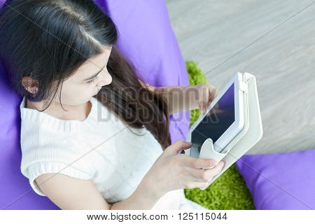 little girl reading e-book while lying on the floor. Reading e-books. Education, leisure, technology and the concept of the Internet - a little girl with a tablet PC at home.