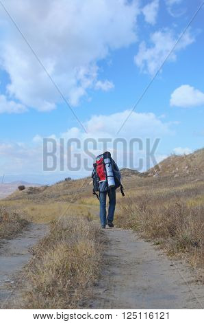 A tourist walks along a trail in the Mongolian steppe.