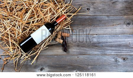 Overhead view of a red wine bottle on top of straw with vintage wine corkscrew and corks.