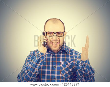Angry man in glasses yells into  phone. Isolated on gray background.