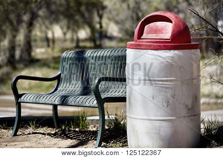 empty park bench and rubbish can with lid on forest trail and park