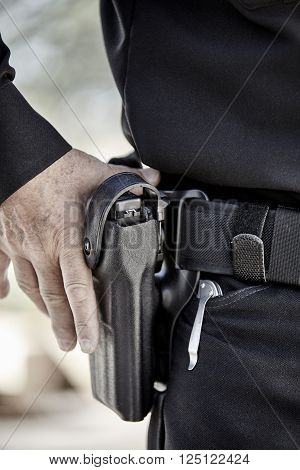 law enforcement police man with hand on weapon gun