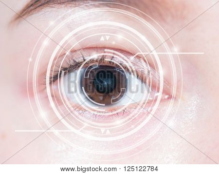 Close-up of woman's brown eye. High technology in the futuristic. scan, contact lens