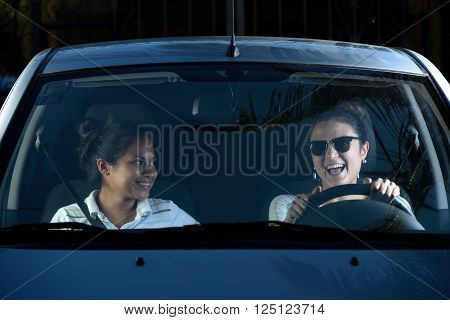 Woman driving with her friend a car in a sunny day