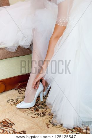 bridesmaid helping bride to put on elegant shoes