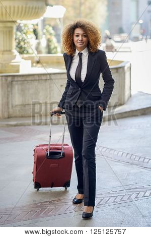 Beautiful black woman smiling and carrying a rolling suitcase in urban background Businesswoman wearing suit with trousers and tie, afro hairstyle.