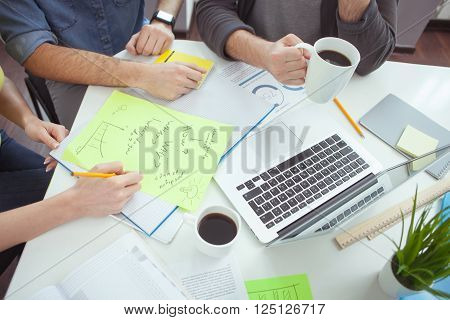 Close up of arms of cheerful young team working on new project. Woman is sitting at the desk and writing some notes on paper. Man is holding a cup of coffee