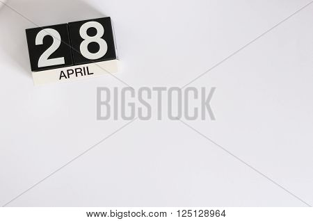 April 28th. Tax Day. Image of april 28 wooden color calendar on white background.  Spring day, empty space for text.