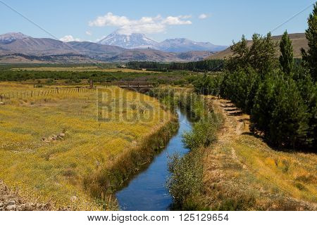 Patagonian runnel with a bridge and volcano Lanin at bottom