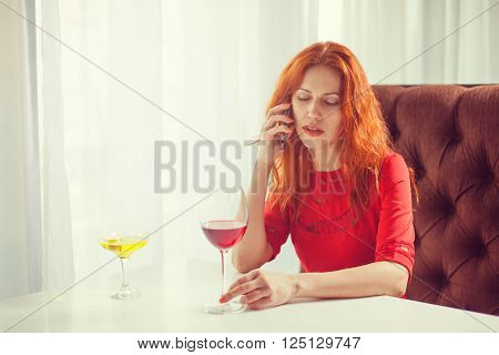 Beautiful girl talking on the phone in a cafe and drink wine.