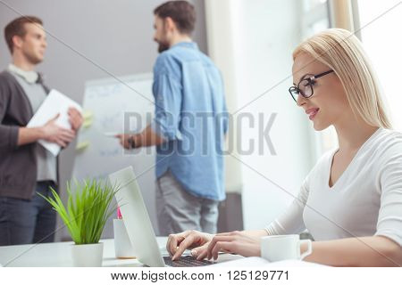 Beautiful young businesswoman is typing on a laptop in office. She is sitting at desk and smiling. Her male colleagues are standing and talking on background