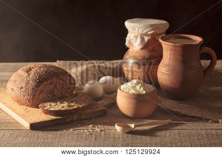 Rustic still life. The morning sun from the window. Country breakfast. Jug with milk black bread cheese eggs a wooden table.