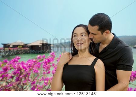 Happy interracial couple in love at sea side with bungalow background .Summer holidaysvacation travel and dating concept. Asian womanCaucasian man