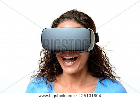 Woman wearing a pair of virtual reality goggles while she is laughing
