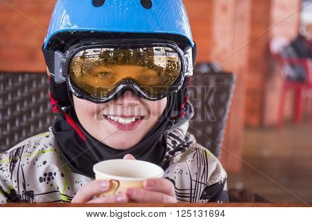 Portrait of a boy in ski helmet and protective glasses drinking tea