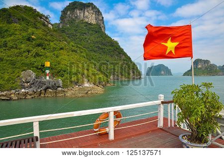 Vietnam flag on the background of the islands of Halong Bay.