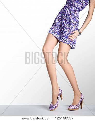 Woman in fashion dress and high heels. Perfect female sexy long legs, stylish purple flower sundress and summer glamour shoes. Unusual creative elegant walking out outfit, people.  Vintage, copy space