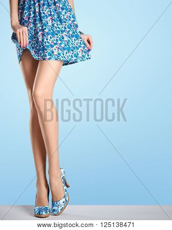 Woman long legs in fashion dress, high heels. Perfect female  sexy legs, stylish blue flower skirt and summer glamour shoes. Unusual creative elegant walking out outfit, people. Vintage, copy space