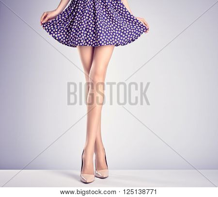 Woman long legs in fashion dress and high heels. Perfect female  sexy legs, stylish purple skirt and summer glamour shoes. Unusual creative elegant walking out outfit, people.  Vintage, copy space