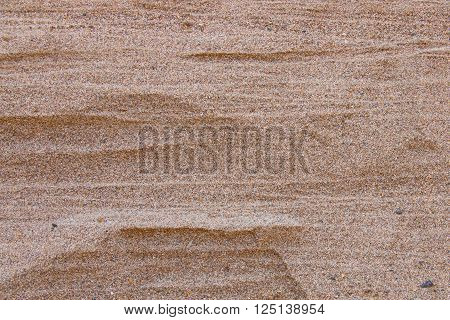Close up of sand pattern of a beach in the summer. Quarry sand wall close up. Sand background