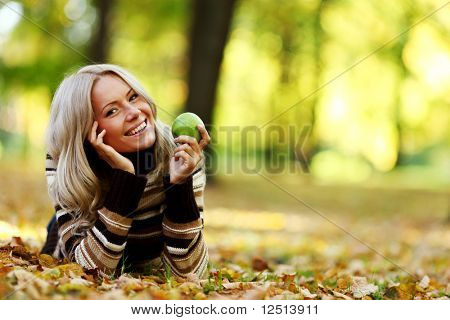 eat apple in autumn park