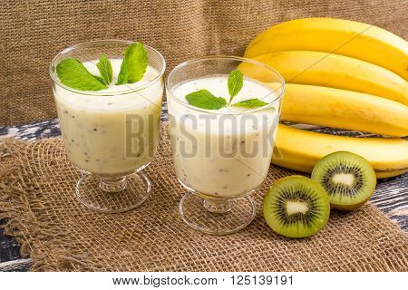 Cocktail from a kiwi and banana in two glasses on an old table