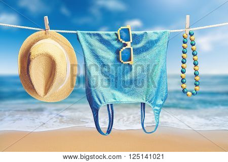Beach outfit. Summer clothes and accessories stylish set. Fashion swimsuit, sunglasses, hat necklace on rope. Essentials creative look on tropical sea sky background. Hawaii, ocean vacation concept