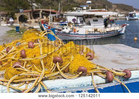 Fishing nets and Greek fishing boats mooring in port in sunrise light Crete island Greece
