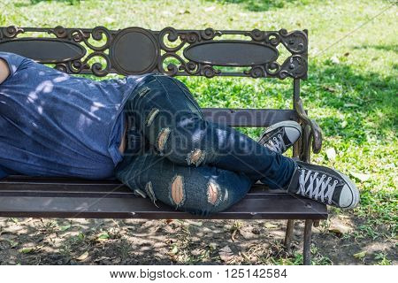 Homeless man is sleeping on a bench in the park.