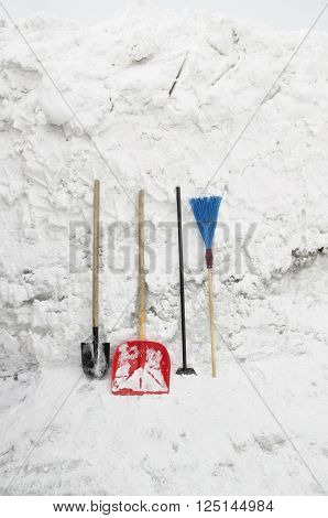 Tools for clearing snow on a background of a snowdrift.