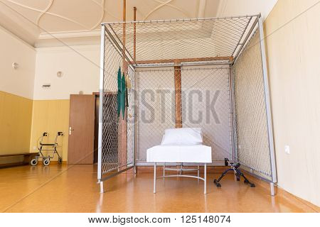 Sofia, Bulgaria - April 7, 2016: A room in a rehabilitation centre part of a military hospital. A bed in a metal cage.