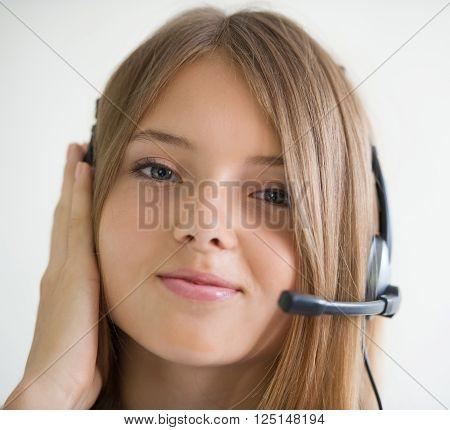 girl secretary talking on the speakerphone on light background