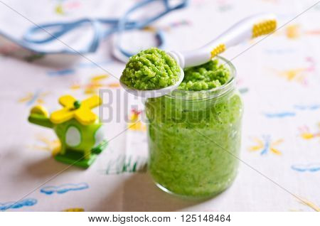 Baby food of peas on the table against the background of toys. Selective focus.