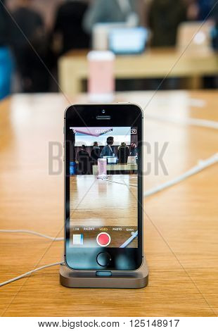 STRASBOURG FRANCE - APR 9 2016: New iPhone SE in docking station recording Apple Store with camera app. New Apple iPhone tends to become one of the most popular smart phones in the world.