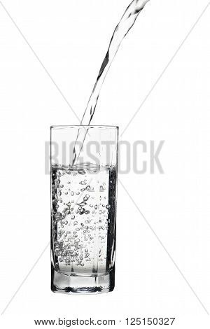 Water pouring into glass air bubbles in the water isolated on white background