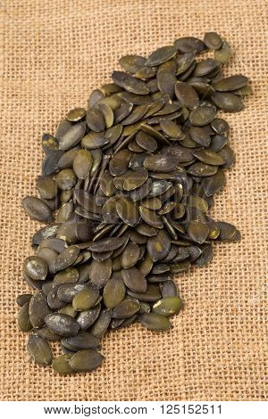 Heap of unshelled pumpkin seeds on burlap background