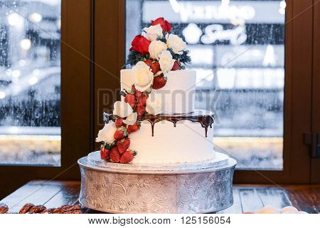 A 3 tiered cake with strawberries and chocolate, a rainy day in the background.