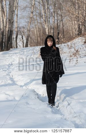 the girl in a black fur coat goes on a snow-covered footpath