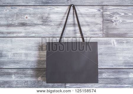 Blank black shopping bag hanging on wooden wall. Mock up