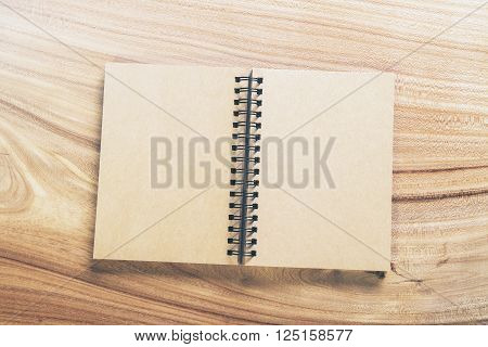 Top view of blank aged notepad on wooden table. Mock up