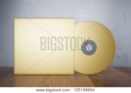 Blank golden compact disk with cover on wooden table and concrete wall background. Mock up, 3D Rendering