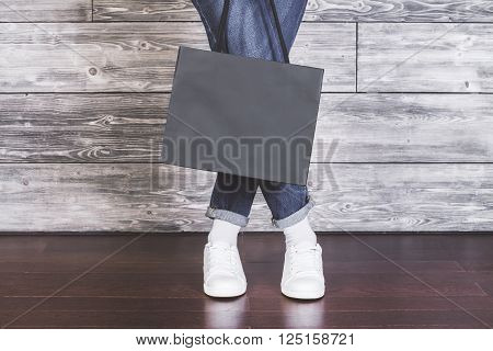Closeup of female legs with blank shopping bag on wooden background. Mock up