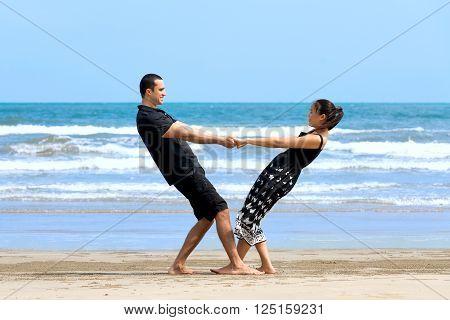 Couple enjoying on beach.Young happy interracial couple enjoying on beach and smiling to each other. Asian womanCaucasian man